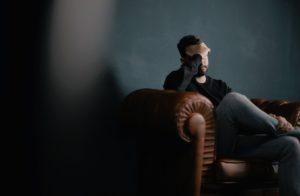 Schlaganfall - Mann, der die Hand vors Gesicht hält