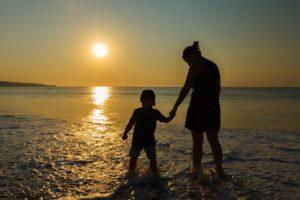 Fördere ich mein Kind genug? - Mama mit Kind am Strand