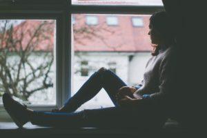 komisch angestarrt werden - traurige Frau am Fenster